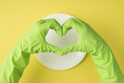 Overhead pov photo of dish and hands in green gloves as heart isolated on the yellow background