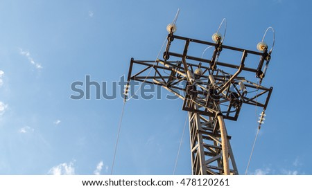 Overhead power line tower on a slightly cloudy blue sky background. #478120261