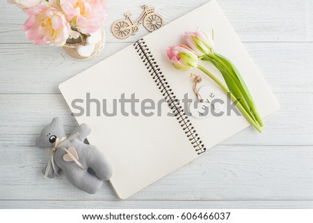 Overhead shot a bouquet of pink tulips and teddy bear over white wood table top with an open journal. Flat lay top view style.