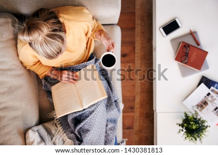 Overhead Shot Looking Down On Woman At Home Lying On Reading Book And Drinking Coffee #1430381813