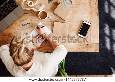Photo of  Overhead Shot Looking Down On Woman Writing In Generic Thank You Card