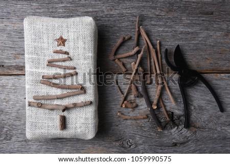 Overhead shot of a burlap wrapped Christmas present with a twig tree and star. Assorted twigs and pruning shears are also on the rustic wood table. #1059990575