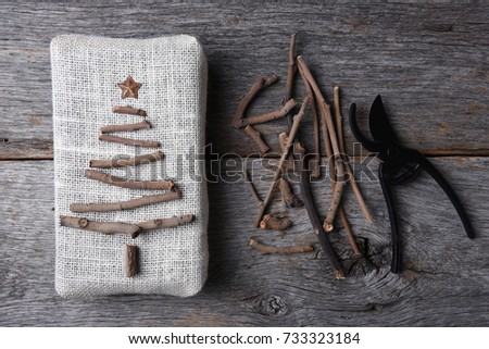 Overhead shot of a burlap wrapped Christmas present with a twig tree and star. Assorted twigs and pruning shears are also on the rustic wood table. #733323184
