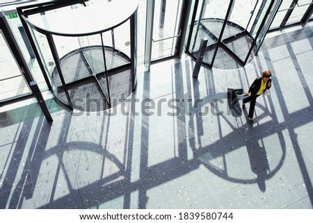 Overhead shot of a businesswoman walking through revolving door with a suitcase in her hand with copy space available.