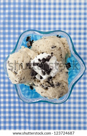 Overhead shot of a cookies and cream ice cream on a blue cup