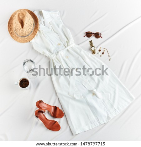 Overhead shot of a female summer clothes and accessories on white desktop.top view. fashion, style concept