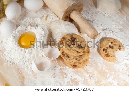 Overhead shot of a few cookies , raw egg and wooden rolling pin