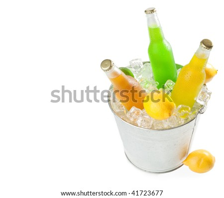 Overhead shot of a metal bucket full with ice cubes and three wet glass bottles with tropical fruit