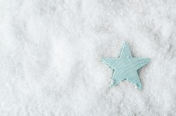Overhead shot of a pale blue wooden star on artificial white snow background with copy space to the left. Christmas background.