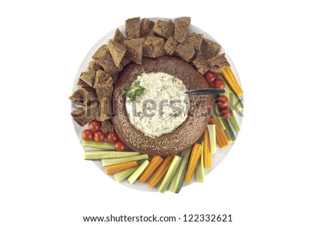 Overhead shot of a plate with pumpernickel bread and spinach dip surrounded by slice vegetables - stock photo