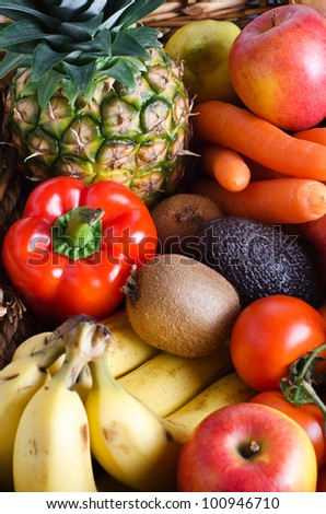 Overhead shot of a selection of fresh fruit and vegetables in a wicker basket.  Portrait orientation.
