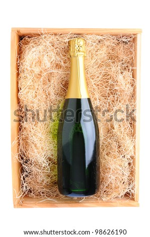 Overhead shot of a single champagne bottle in a wood shipping crate filled with packing straw. Vertical format over a white background Stock photo ©