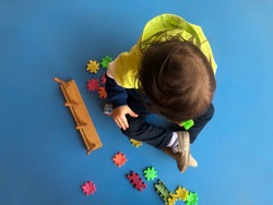 Overhead shot of a toddler looking and playing with jigsaw puzzle
