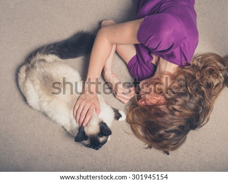 Overhead shot of a young woman lying on a carpet at home and petting a cat