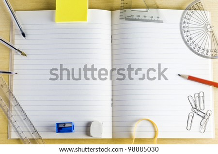 Overhead shot of an opened school exercise book. surrounded by stationery items on a light wood desk. Lined pages provide copy space.