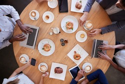 Overhead Shot Of Businesspeople Meeting In Coffee Shop