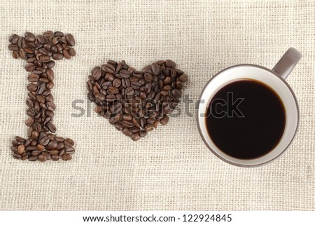 Overhead shot of coffee beans and coffee cup arranged to form I love you.