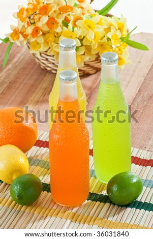 Overhead shot of cold drinks with fruits around them on wooden table