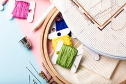 Overhead shot of embroidery set fot cross stitching. White fabric, embroidery hoop, colorful threads, scissors and needls. On pink blue background. Hobbies concept with copy space.
