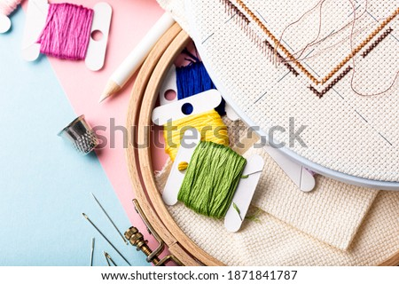 Overhead shot of embroidery set fot cross stitching. White fabric, embroidery hoop, colorful threads, scissors and needls. On pink blue background. Hobbies concept with copy space. Stock fotó ©