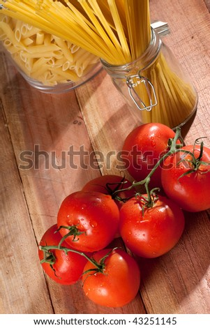Overhead shot of fresh tomatoes next to a glass container with raw pasta