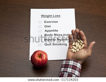 Overhead shot of handful of capsules with an apple and weight loss schedule paper on wooden table.