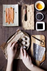 overhead shot of hands slicing a roll of hosomaki sushi and ingredients on table