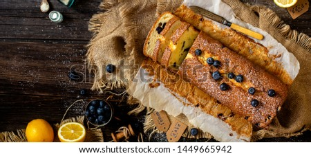 Overhead shot of homemade sliced rectangular baked lemon cake with blueberries on paper and sackcloth on rustic wooden table with bottle of spices, cup of berries, lemons, strainer, knife #1449665942
