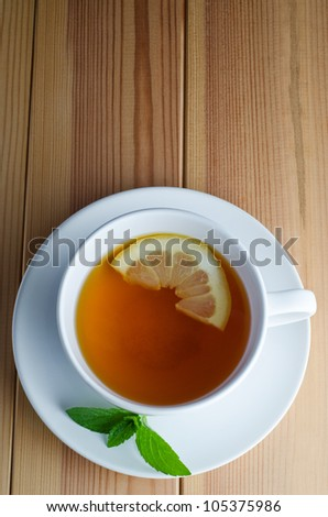 Overhead shot of lemon tea in a white cup and saucer with half a lemon slice and mint leaves on a wooden planked table.