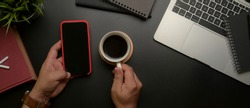 Overhead shot of male entrepreneur left hand using smartphone while right hand holding coffee cup on dark modern office desk