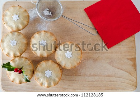 Overhead shot of mince pies decorated with holly sprig and sifted icing sugar in star shapes.  An old tea straining sieve sits on wooden board with sprinkled icing sugar. Red napkin on upper right.