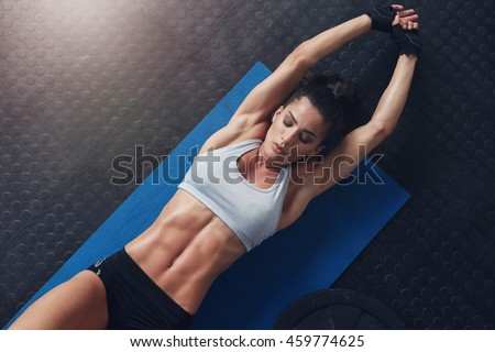 Shutterstock Overhead shot of muscular and fit young woman doing stretching workout exercise mat. Fitness female lying on mat with stretching her hands.