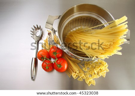 Overhead shot of pasta, tomatoes and pot on stainless steel counter
