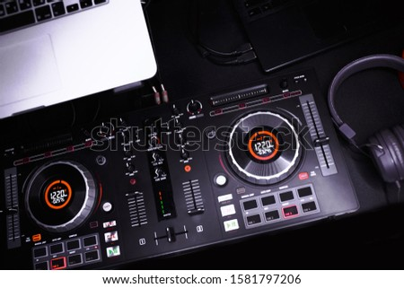 Overhead shot of red party dj audio equipment.Turntable top view.Professional concert DJ top view.High quality mixing controller disc jockey in night club.Pro audio equipment on stage in nightclub