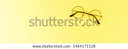 Overhead shot of round eyeglasses on yellow table with copyspace. Banner