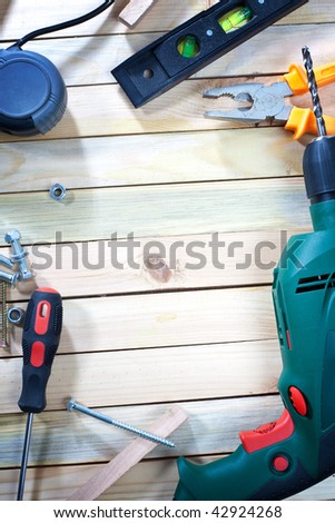 Overhead shot of screw driver, screws and drill on wooden table with empty space for your text