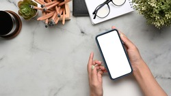 Overhead shot of woman holding mock up smart phone with white screen at marble background.