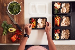 Overhead Shot Of Woman Preparing Batch Of Healthy Meals At Home In Kitchen