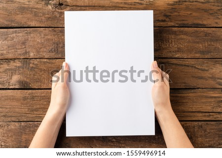 Overhead shot of woman's hands holding blank paper sheet on rustic wooden table. Close up 商業照片 ©