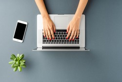 Overhead shot of woman's hands working on laptop on gray table with smart phone and green flower. Office desktop. Flat lay