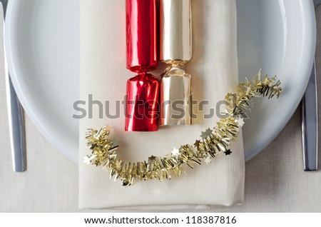 Overhead shot representing Christmas dinner, with red and gold crackers and tinsel laid on a napkin, with plate, cutlery and tablecloth underneath.