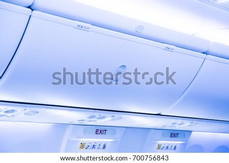 Overhead stowage or overhead bin and emergency exit door in modern airplane jet. #700756843