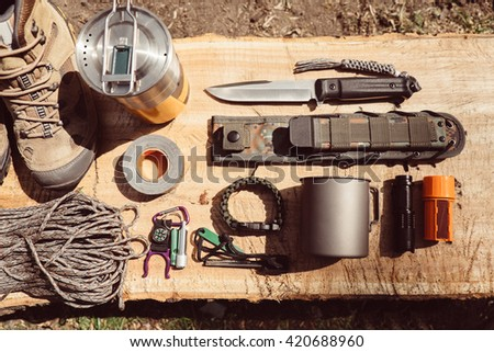 Overhead top view of hiking travel gear on wood log. Items include hiking boots, cup, rope, knife, matches, flashlight, compass. Flat lay of outdoor travel equipment items for mountain camping trip.