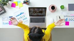 Overhead top view young asian woman employee work from home using computer notebook videocall meeting conference angry annoy with low poor unreliable internet wifi connection problem issue outage.