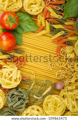 Overhead various Italian pasta background with tomatoes, basil and garlic