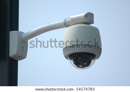 Overhead video security camera mounted on a pole, against a blue sky