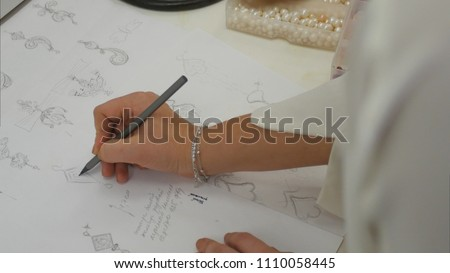 Overhead view looking down jewelry designer in studio sketching out designs #1110058445