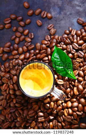 Overhead view of a cup of rich frothy coffee standing in scattered whole roasted coffee beans with a green leaf for decoration