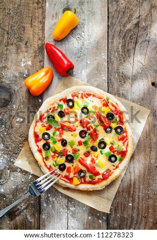 Overhead view of a delicious colourful homebaked pizza with a thick golden crust and topped with cheese, peppers, tomatoes and olives