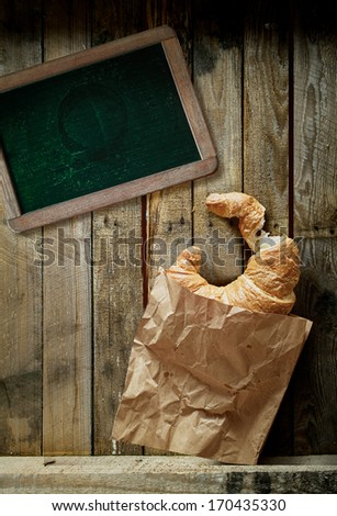 Overhead view of a freshly baked golden croissant, a cup of full roast espresso coffee and an old blank school slate for a menu or text on rustic wooden boards